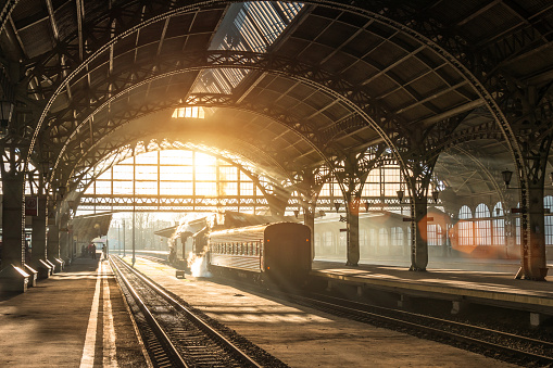 Old railway station with a train and a locomotive on the platform awaiting departure. Evening sunshine rays in smoke arches.