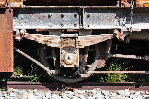 The rusting wheel and suspension of an old railway wagon
