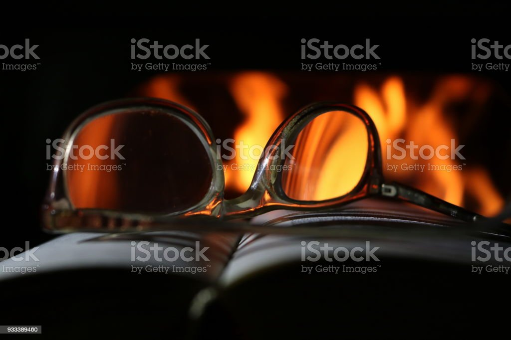 Old Reading Glasses On Old Book And Fireplace stock photo