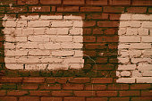 Old realistic dirty brick wall made of brown brick. Uneven brickwork. Part of wall is painted beige. Two rectangles for mock close-up.