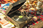 Old record player in second hand market, plaques, old books and small items, cups and porcelain teapots