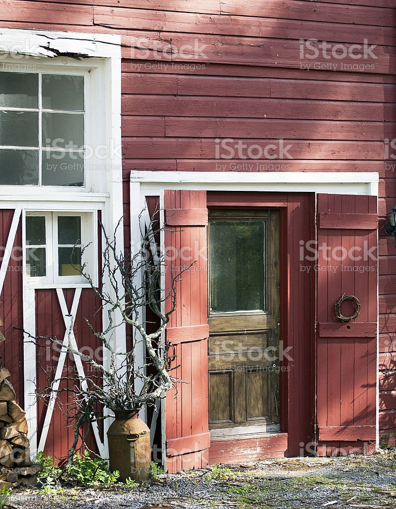 Old Red Barn Entrance with sculptural elements in afternoon light. royalty-free stock photo