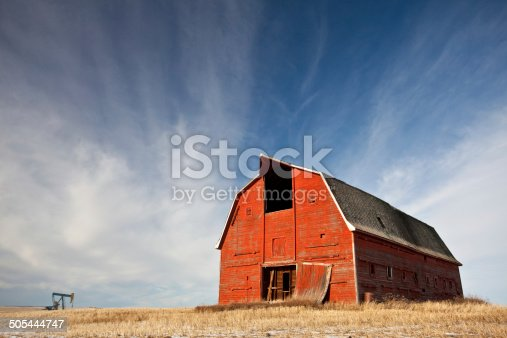 A classic red barn on the plains. Dramatic evening lighting. Rural Alberta scenic. Pumpjack is also in the image. These are both common subjects in rural alberta, where both agriculture and the oil industry are major economic players.