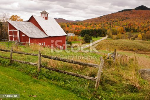 With a valley filled with autumn color, an untended pasture is fenced in beside an old red barn in northern Vermont.