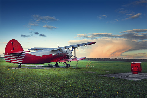 Old red biplane on a green field at sunset