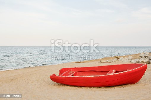 Old red fishing boat on the sandy beach, waves on the water and sky background
