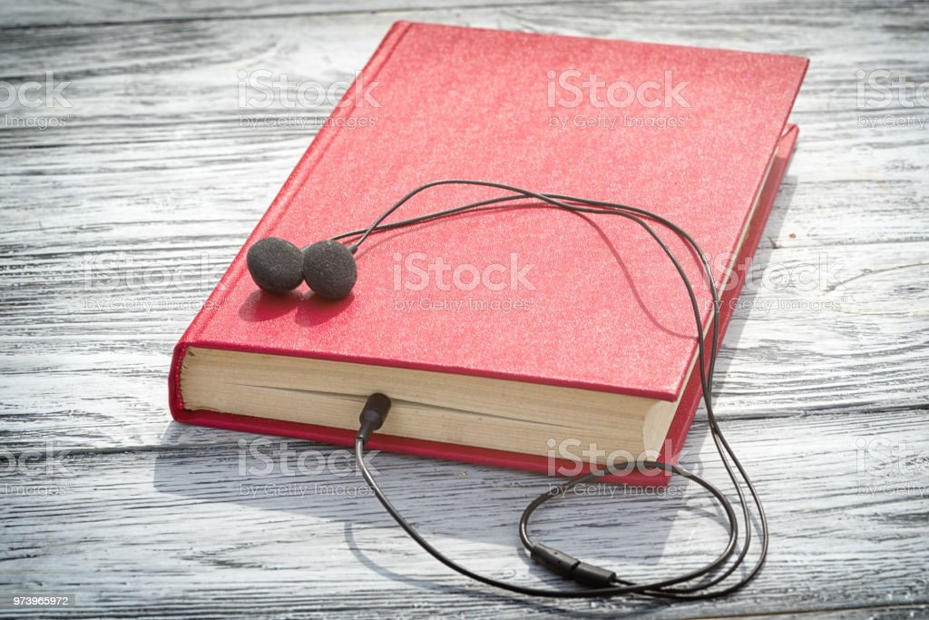 antigo livro vermelho encontra-se em uma mesa de madeira com fones de ouvido nele e copie o espaço para o seu texto. conceito de audiobook. - foto de acervo