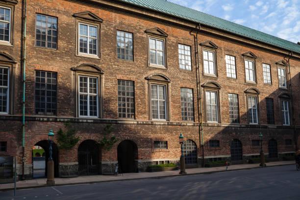 Old red brick building wall of house undera rays of sun. City center of Copenhagen, Denmark stock photo