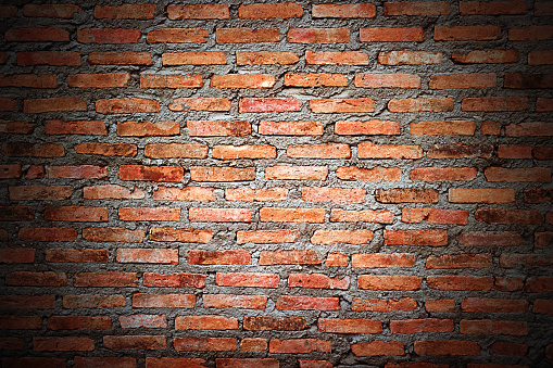 Old red brick wall texture grunge background with vignetted corner background