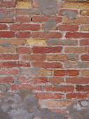 an old red brick wall with mixed colored bricks and signs of damage and repairing with cement