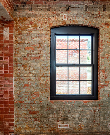Metal window with top arch set within old brink wall