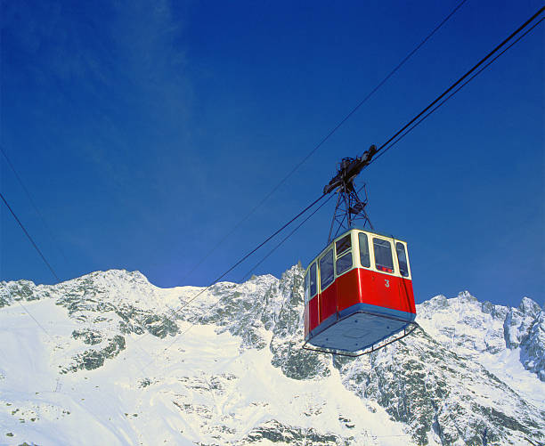Old red cableway, snowy mountains and blue sky on background stock photo