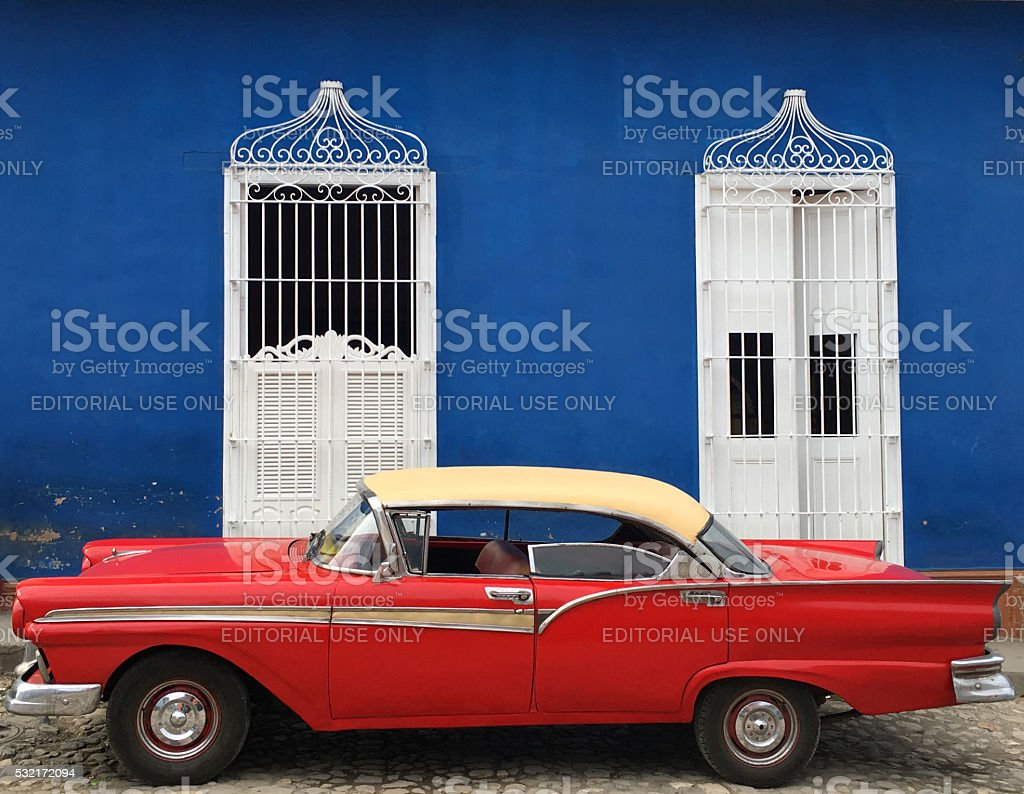 Old red car Trinidad, Cuba - April 25, 2016: Old red Ford parking in front of blue house on the street of city center of Trinidad, Cuba. Blue Stock Photo