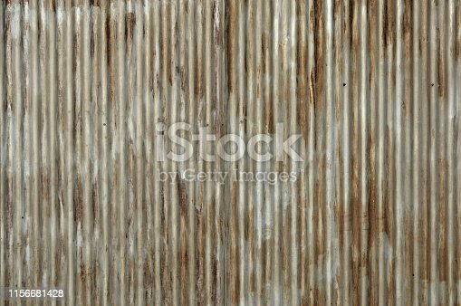 istock Old red metal roof of the building, a lot of damage on the metal, closeup texture or background 1156681428