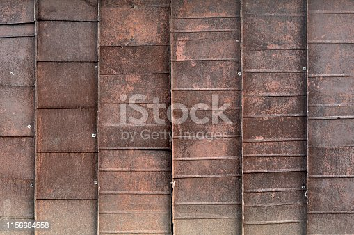 istock Old red metal roof of the building, a lot of damage on the metal, closeup texture or background 1156684558