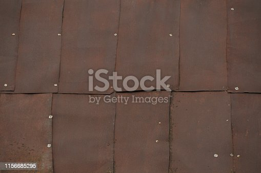 istock Old red metal roof of the building, a lot of damage on the metal, closeup texture or background 1156685295