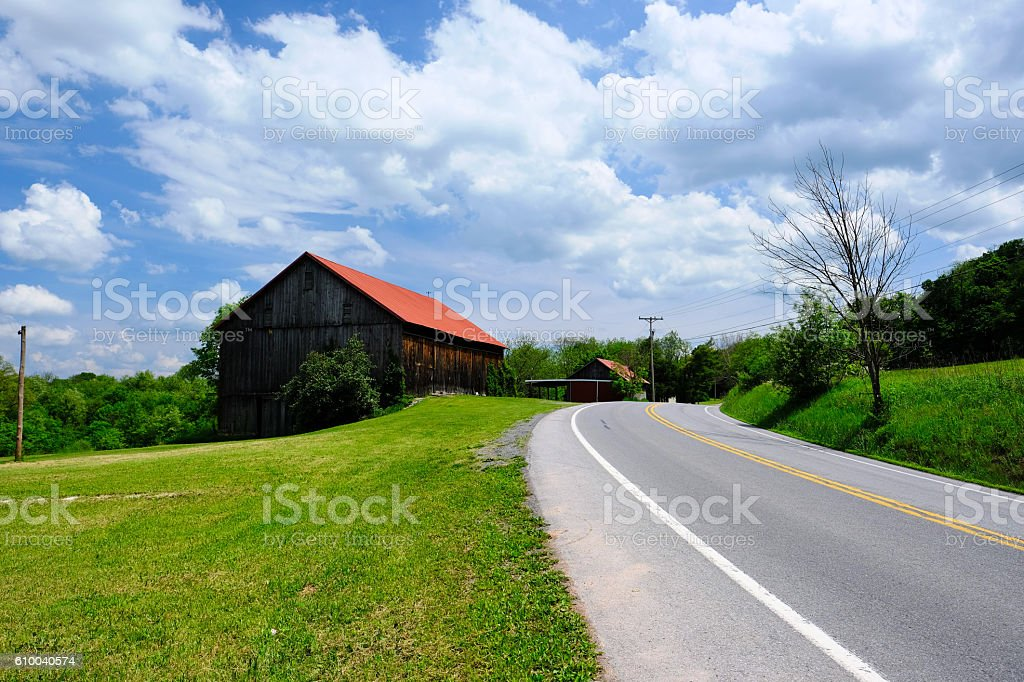 Old red roof barn near highway stock photo