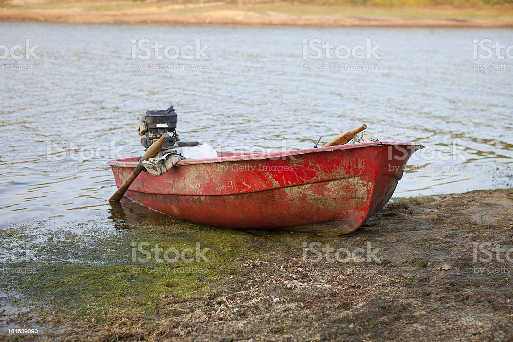 old red rowboat by the lake stock photo