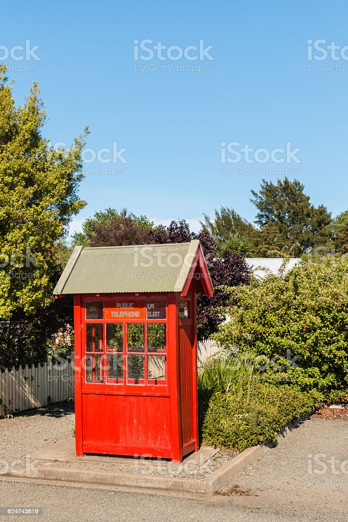 old red telephone booth in garden stock photo