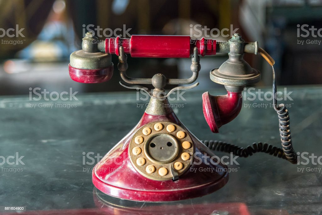 Old red telephone with rotary dial on glass table. stock photo