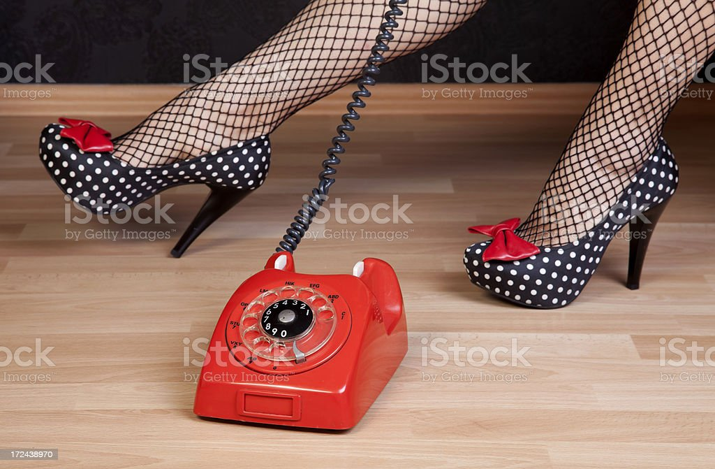 Old red telephone with woman leg royalty-free stock photo