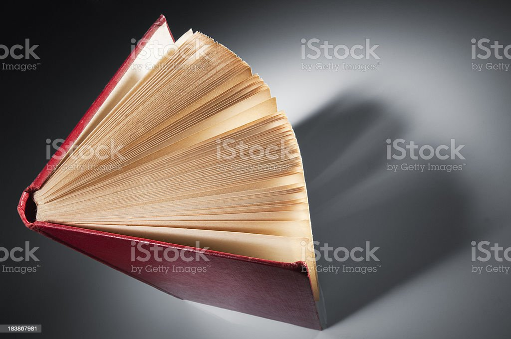 Old red vintage book stood slightly fanned in spotlight royalty-free stock photo