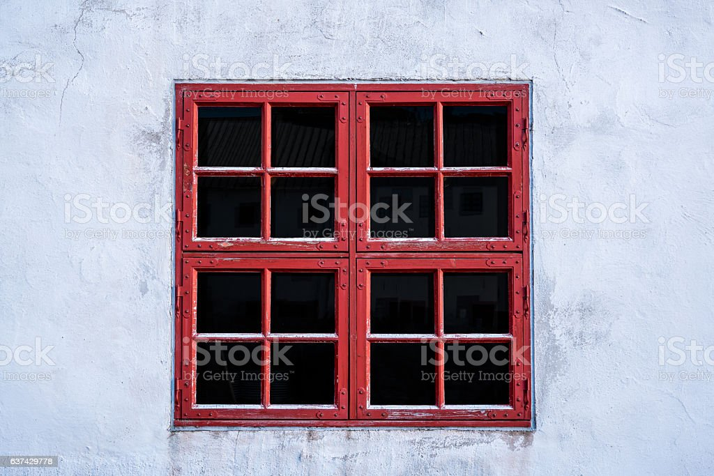 Old red weathered window with squares on white wall. stock photo