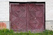 Old red wooden garage gate in the thrown brick rural house. Sunny summer day