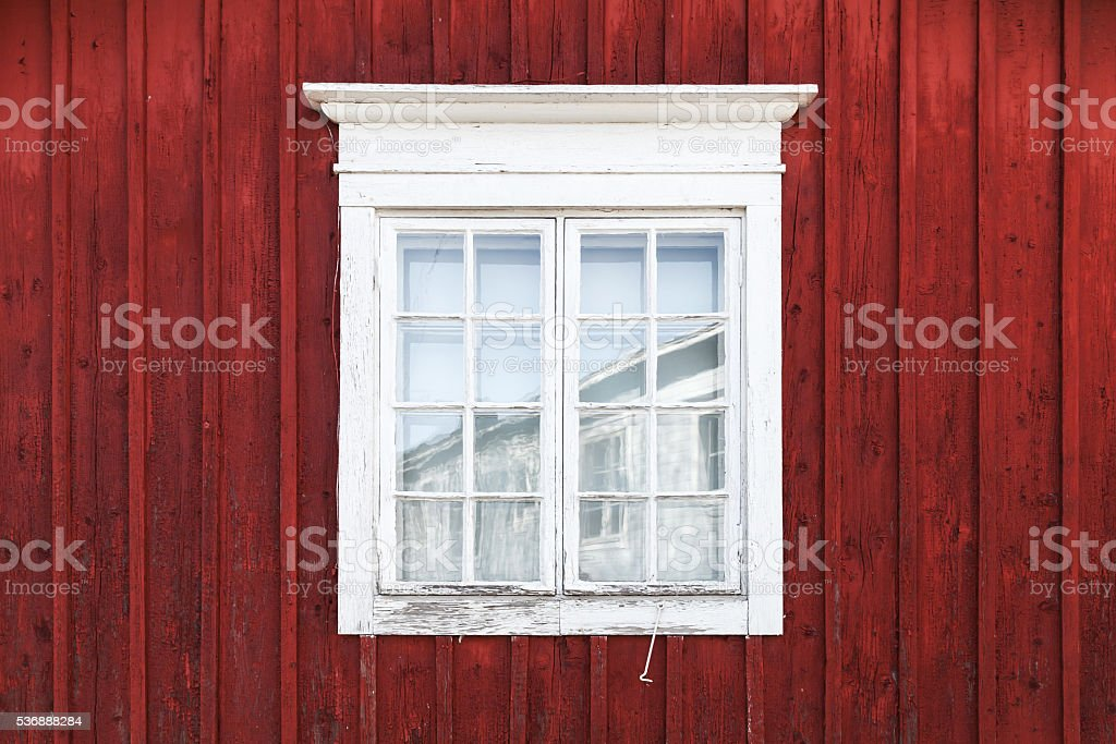 Old red wooden wall with window in white frame, typically...