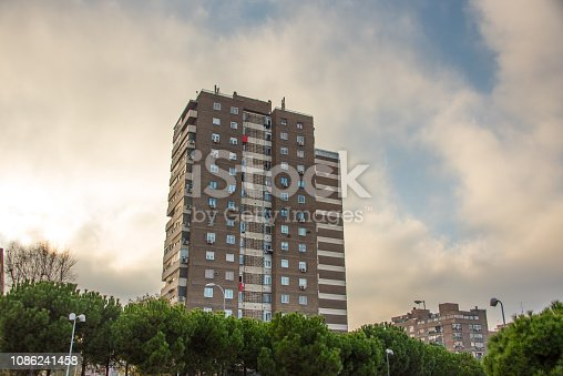 An old, tall residential building in Madrid, Spain, against a dramatic sunset sky
