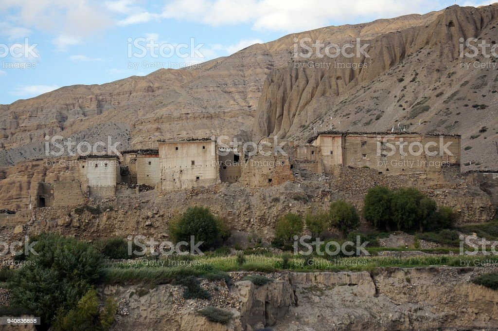 Old residential houses in Chhusang, against the backdrop of the mountain. stock photo