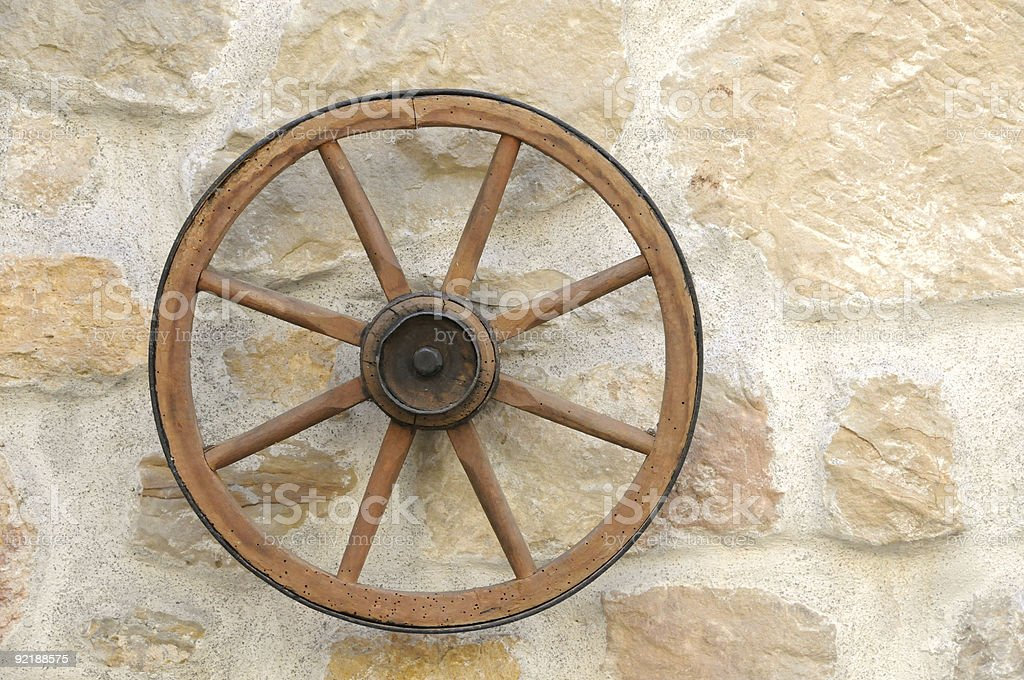 Old restored clean wagon wheel on stone wall close up royalty-free stock photo