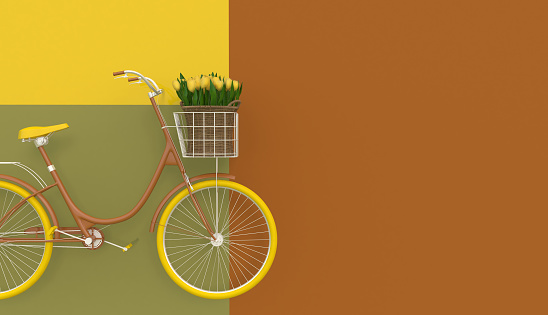 Old retro bicycle in brown with yellow wheels and yellow flowers in a basket on a colorful background. Copy space.  Abstract concept.