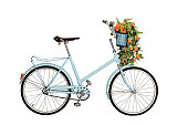 Old retro blue bicycle with flowers bouquet in basket isolated on white background