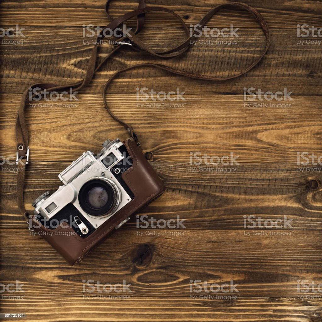 Old retro camera on vintage rustic wooden planks boards. Education photography courses back to  school concept abstract background. Close up, top view, copy space. stock photo
