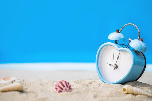 old retro clock on sand beach stock photo