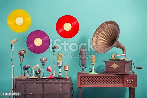istock Old retro microphones, antique gramophone phonograph turntable with brass horn, flying multicolor LP vinyl record discs front blue background. Nostalgia music concept. Vintage style filtered photo 1160115889