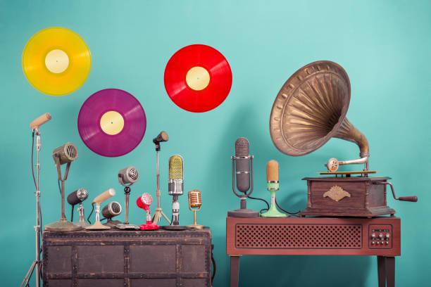Alte Retro-Mikrofone, antike Grammophon Phonograph Plattenspieler mit Messinghorn, fliegende multicolor LP Vinyl Schallplatten Scheiben vordem blauen Hintergrund. Nostalgie-Musik-Konzept. Vintage-Stil gefiltertfoto – Foto