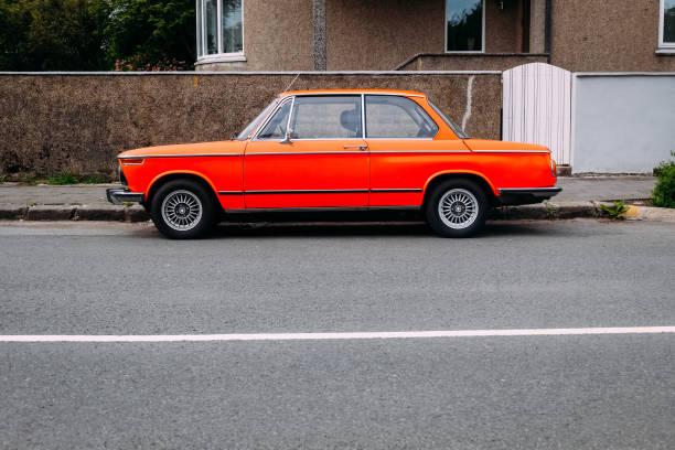 altes retro orange Auto in der Nähe der Straße im Sommer an einem sonnigen Tag geparkt – Foto