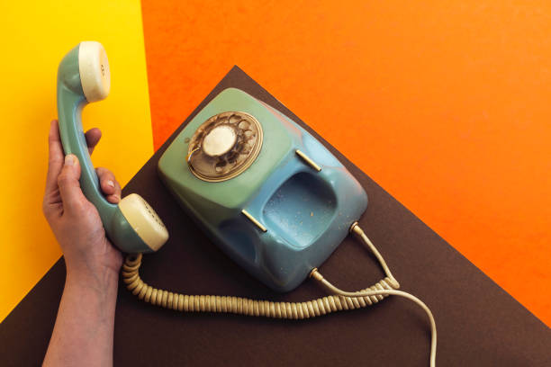 old retro phone isolated on colorful background and hand holding handset - hand holding phone zdjęcia i obrazy z banku zdjęć