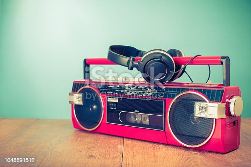 1043737676 istock photo Old retro red stereo radio cassette recorder and headphones. Vintage style filtered photo 1048891512