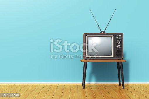 istock Old retro TV against blue vintage wall in the room 997124740