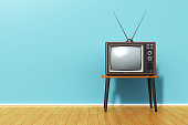 Creative abstract 3D render illustration of the old retro TV television set with antenna on table against blue vintage wall background and wooden plank floor in the room