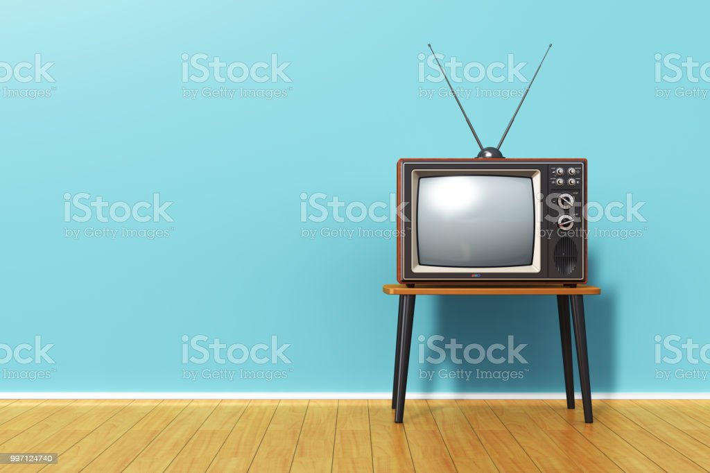 Old retro TV against blue vintage wall in the room stock photo