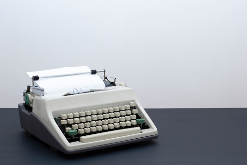 Old retro typewriter on a black wooden table against the background of a light wall.