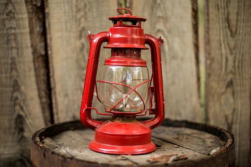 Old retro vinatge style decoration item red kerosene oil lamp on wooden wall background