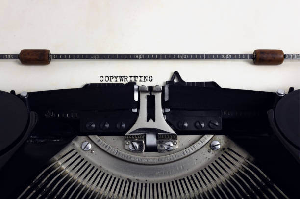 Old retro vintage black typewriter with close-up typing text Copywriting as heading on aged paper Old retro vintage black typewriter with close-up typing text Copywriting as heading on aged paper copywriter stock pictures, royalty-free photos & images