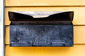 Old retro vintage door mail box, mailbox attached to house home wall exterior painted in yellow color in New Orleans, Louisiana