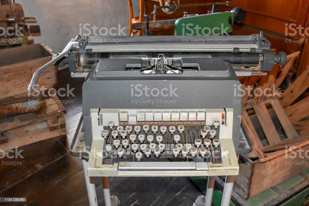Old Vintage type writer machine on a desk in a storage room, retro...