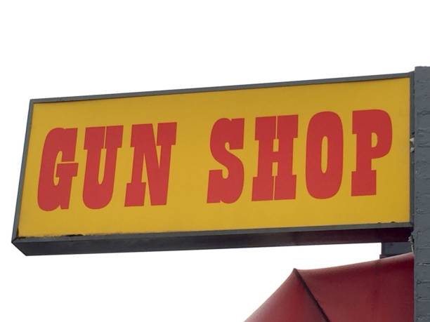 Old retro yellow and red gun shop sign isolated against a white sky Wall mounted sign for a gun shop gun shop stock pictures, royalty-free photos & images